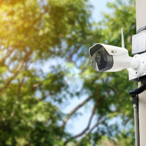 Modern Public Cctv Camera On A Electric Pole With Blurred Natura